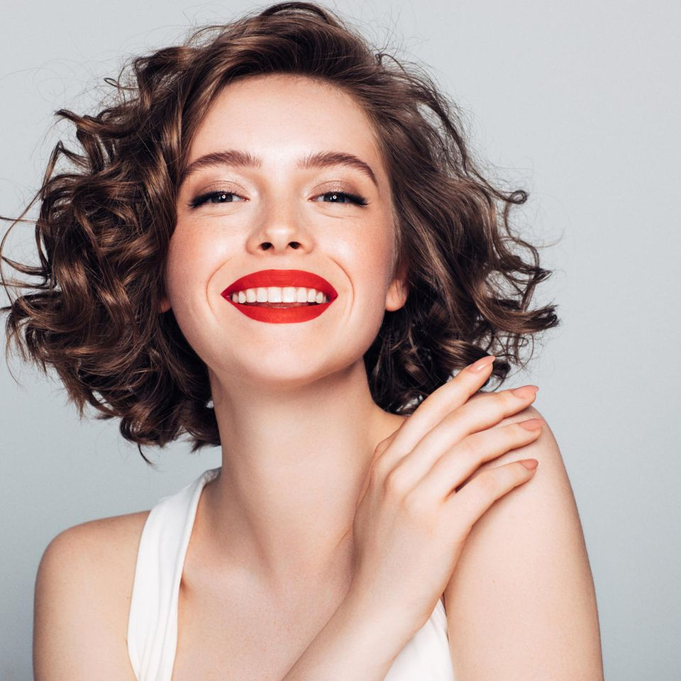Brünette Frau mit rotem Lippenstift strahlt