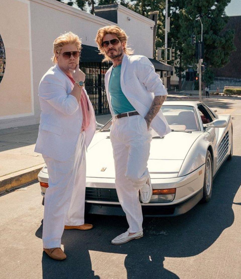 """14. August 2020  Wir kennen David Beckham zwar als lässigen Typen, aber dieser sommerliche Look überrascht uns dann doch. Der Grund für dieVerkleidung: Für eine Episode seinerLate-Night-Showhat sich Talkmaster James Corden den Fußballstar an seine Seite geholt. Als Hommage an die 80er-Kultserie """"Miami Vice"""" schlüpfen die beiden in die Rollen der coolen Cops, Sonny und Rico, um im weißen Ferrari stilecht auf Verbrecherjagd zu gehen."""