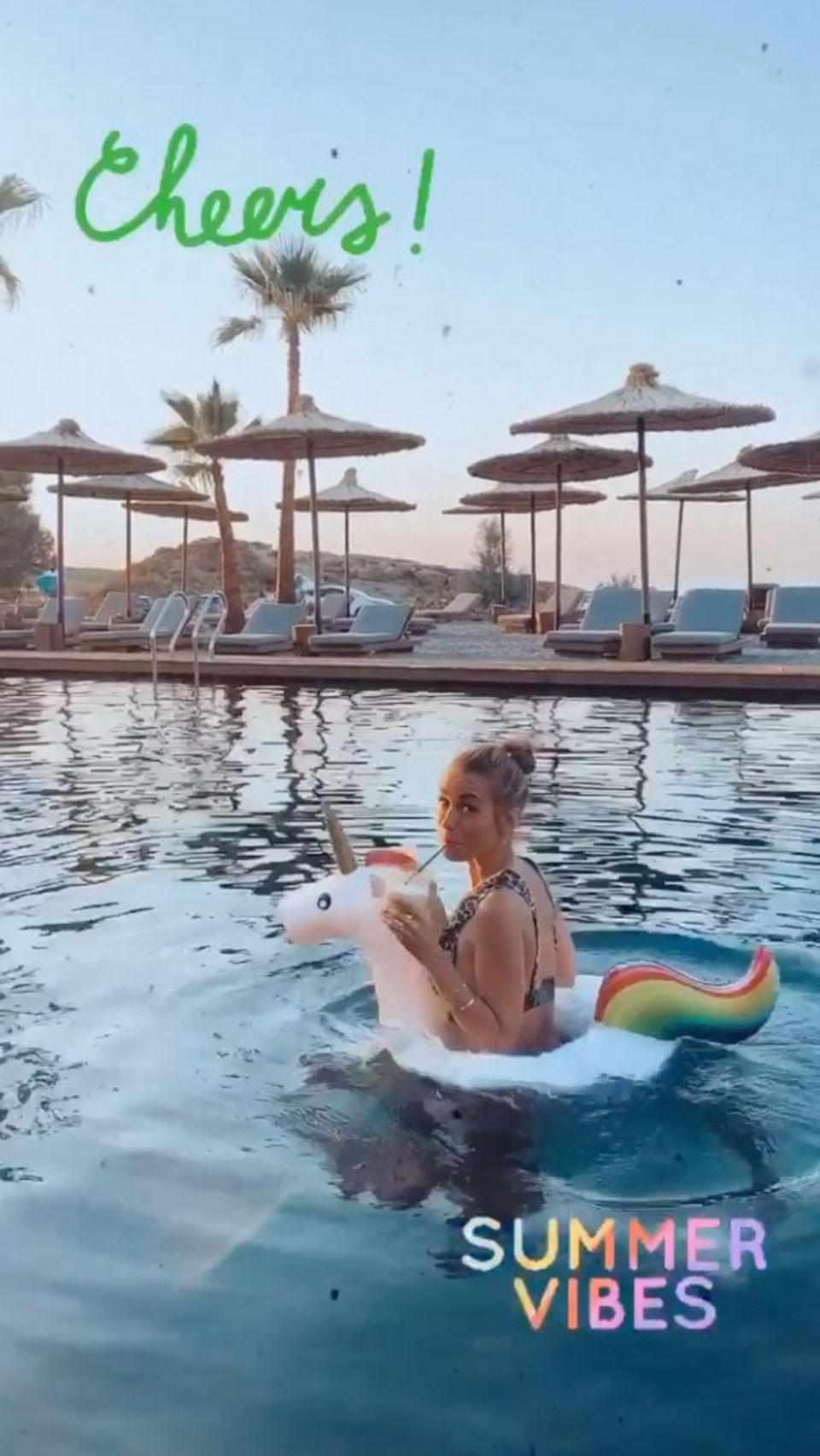 """Mit ihrer Instagram-Story verbreitet Annemarie Carpendale """"Summer Vibes"""" pur: Lässig dreht sie in unter der schönen Abendsonne Griechenlands mit Drink und Einhorn noch eine Runde durch den Pool."""