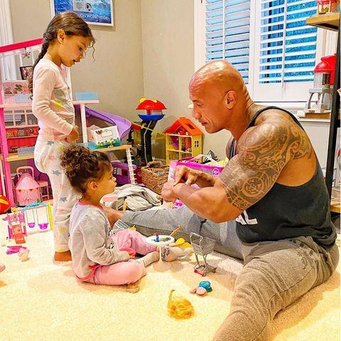 """16. August 2020  Steinhart und ganz, ganz weich: Dwayne Johnson bezaubert sein Instagram-Fams immer wider mit Familienbilder wie diesem. Hier """"erklärt"""" er seinen zwei kleineren Töchtern Tiana und Jasmin, dass er einen großen Dinosaurier bekämpft hat."""