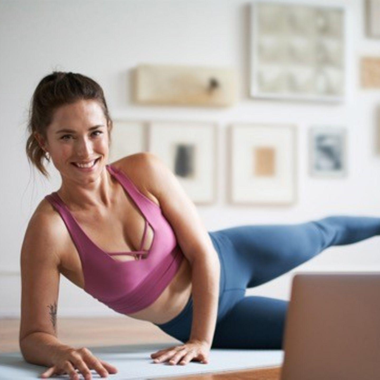 Frau in Sportkleidung macht Fitnessübung zuhause