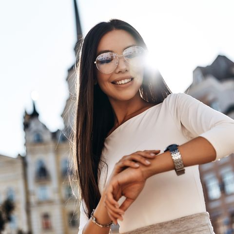 Frau schaut auf Ihre Armbanduhr