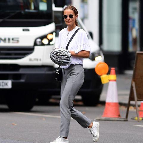 Weiße Bluse, graue Anzughose, weiße Sneaker, schwarze Accessoires: So lässig ist Pippa Middleton in Chelsea unterwegs. Dabei darf ein besonderes Accessoire natürlich nicht fehlen: Ihr Fahrradhelm. Die leidenschaftliche Radlerin setzt immer auf Sicherheit statt Eitelkeit - vorbildlich!
