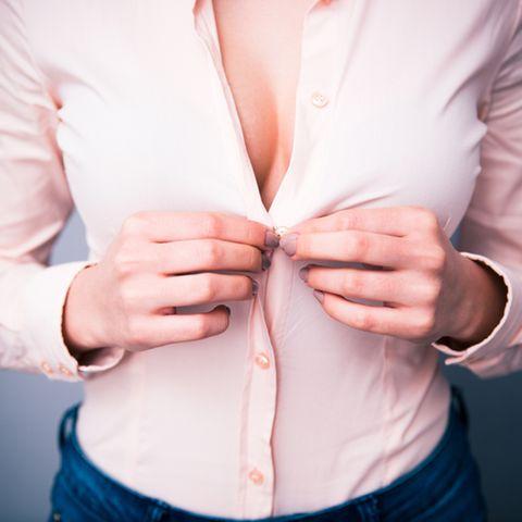 Frau öffnet oberen Teil der Bluse