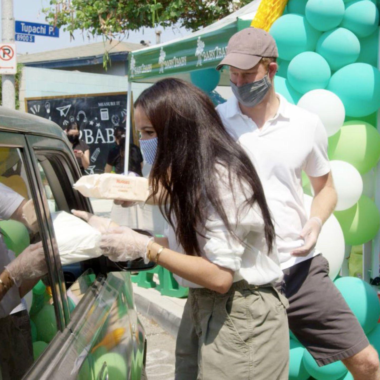 """Ihr großes Herz stellen Herzogin Meghan und Prinz Harry bei dieser wohltätigen Aktion in Los Angeles unter Beweis: Zusammen mit der Organisation """"Baby2Baby"""" händigen sie Schulutensilien, Kleidung und Windeln an Bedürftige aus – natürlich coronakonform mit Maske und genügen Abstand in einem Drive-In. Ein Anlass, zu dem sie sich ganz bodenständig in legerer und schlichter Sommerkleidung zeigen."""