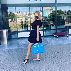 So stylish geht's nach Hause! Victoria Swarovski zeigt am Airport den perfekten Sommerlook aus Volantkleid und Sandalen -Tasche und Gürtel sind auch perfekt aufeinander abgestimmt.
