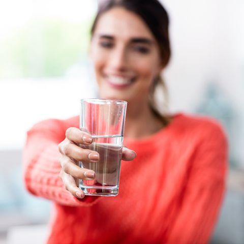 Frau zeigt Trinkglas mit Wasser