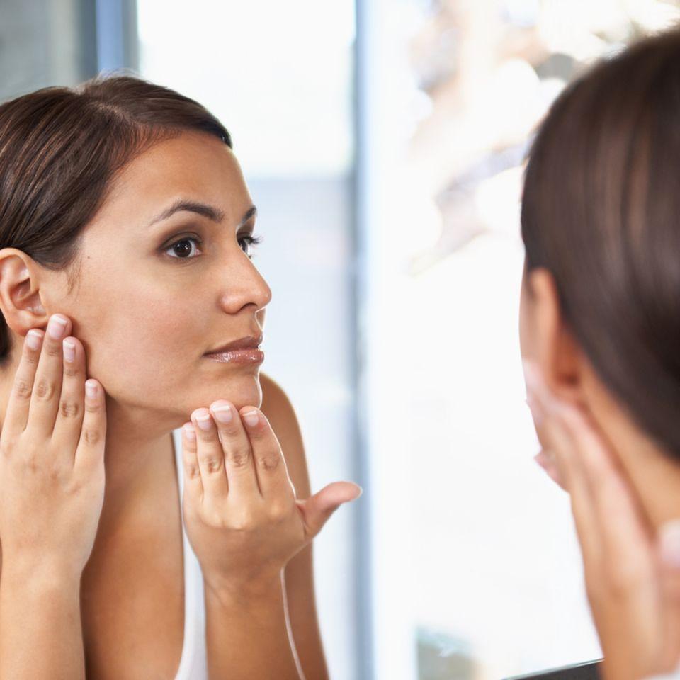 Frau zeigt ebene Haut an Wangen
