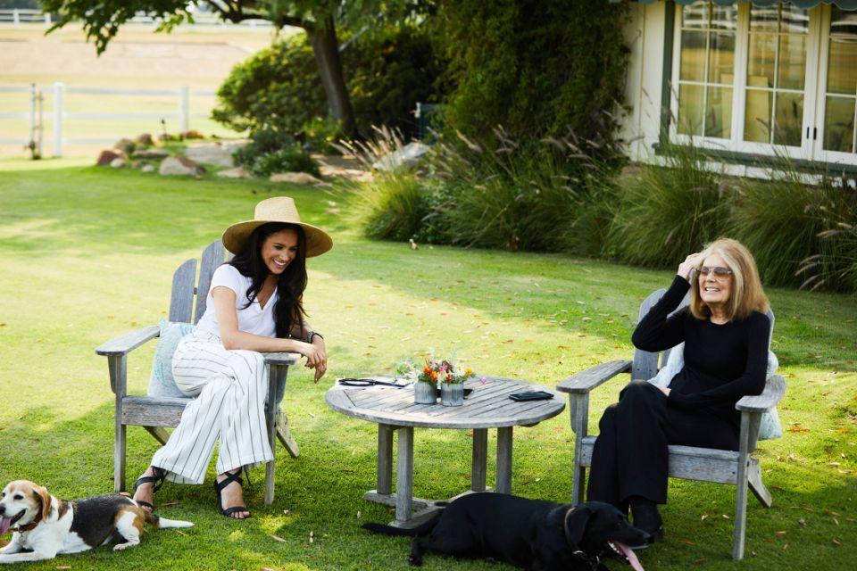 """Meghan setzt auf Frauenpower pur: Sie trägt dieelegante, locker sitzende """"Ryan""""-Stoffhose(rund 210 Euro) von der angesagten Designerin Anine Bing, dazu kombiniert sie ein schlichtes, weißes V-Ausschnitt-Shirt. Ihre sommerlichen """"Rhea""""-Sandalen (rund 673 Euro) stammen von der britischen ModedesignerinStella McCartney, die auch Meghans zweites Hochzeitskleid entworfen hat. Doch damit nicht genug ..."""