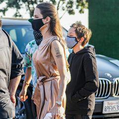 Statt unbemerkt und in Schlabberklamotten ins Restaurant zu gehen, trägt Angelina Jolie ein goldenes Maxi-Kleid, das ihre durchtrainierte Figur sowie ihr Dekolleté perfekt in Szene setzt. Ihre langen, braunen Haare trägt sie offen und nach hinten gesteckt, auf auffällige Accessoires – abgesehen vom Mund-Nasen-Schutz –verzichtet sie. Ein Look, mit dem die 45-Jährige zeigen zu wollen scheint, dass ihr das Liebesleben von ihrem Ex-Mann herzlich egal ist.