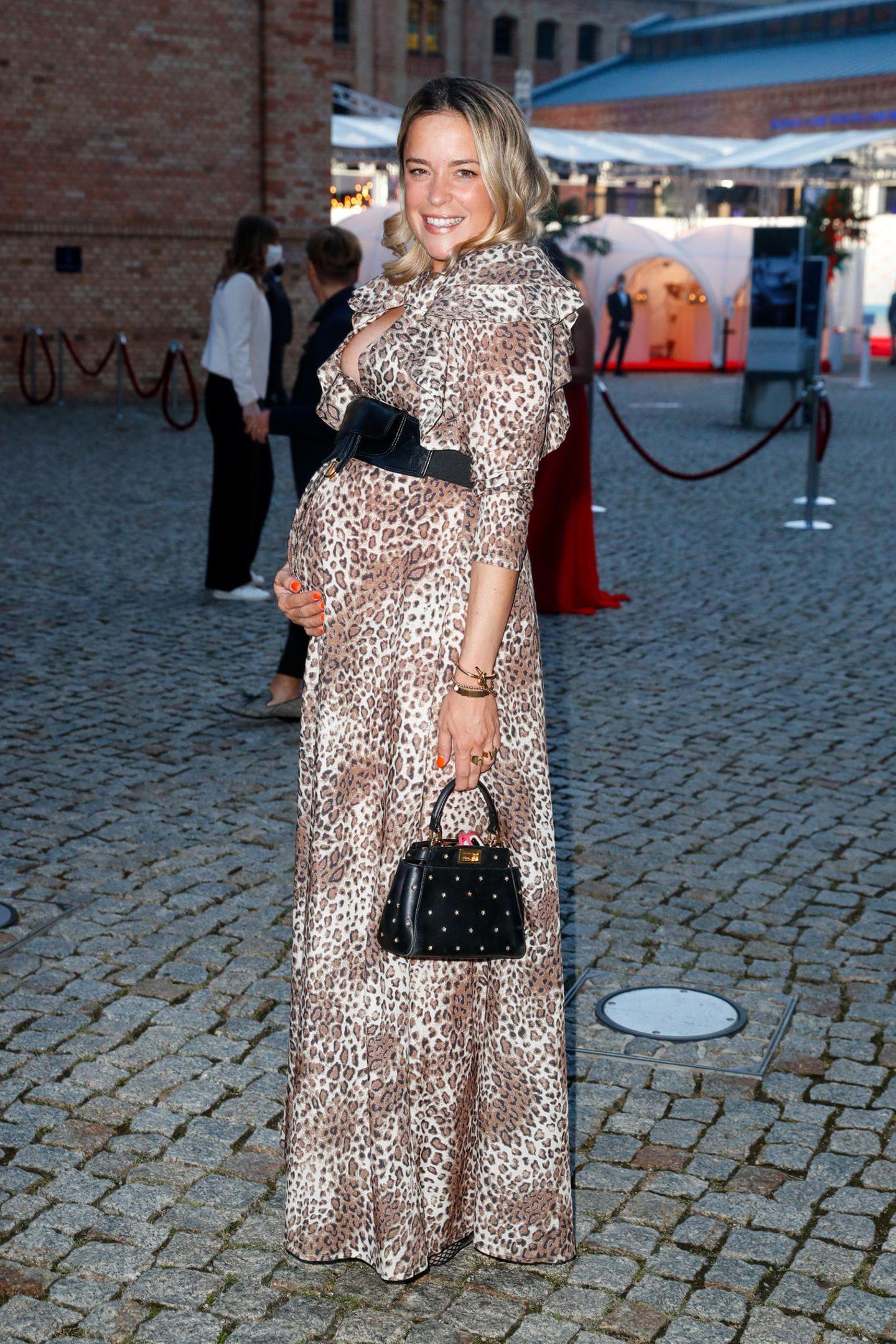 Tierisch schick zeigt sich Marina Hoermanseder beim Raffaello Summer Dinner 2020 in Berlin. Die schwangere Modedesignerin trägt ein edles Maxi-Dress mit Leo-Muster und setzt ihren wachsenden Babybauch mit einem schwarzen Taillengürtel besonders in Szene. Ein tiefer Ausschnitt und XL-Volants an den Schultern unterstreichen zusätzlich ihre feminine Seite. Süßes Detail: Die lackierten Fingernägel in sommerlichem orangerot.