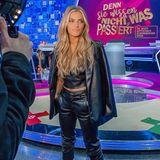 Sophia trägt einen Leder-Anzug bestehend aus hochgesteckter Hose, bauchfreiem Top und Blazer. Helle Pumps strecken ihre Beine optisch und machen den Look perfekt.