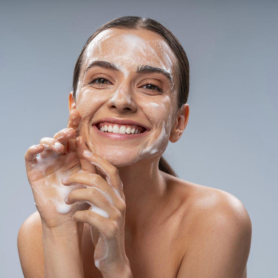 Glückliche Frau reinigt Ihr Gesicht