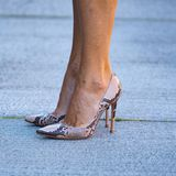 ... an ihrer aufregenden Schuhwahl! Zum eher klassischen Kleid trägt sie Pumps mit Schlangenprint von Gianvito Rossi.