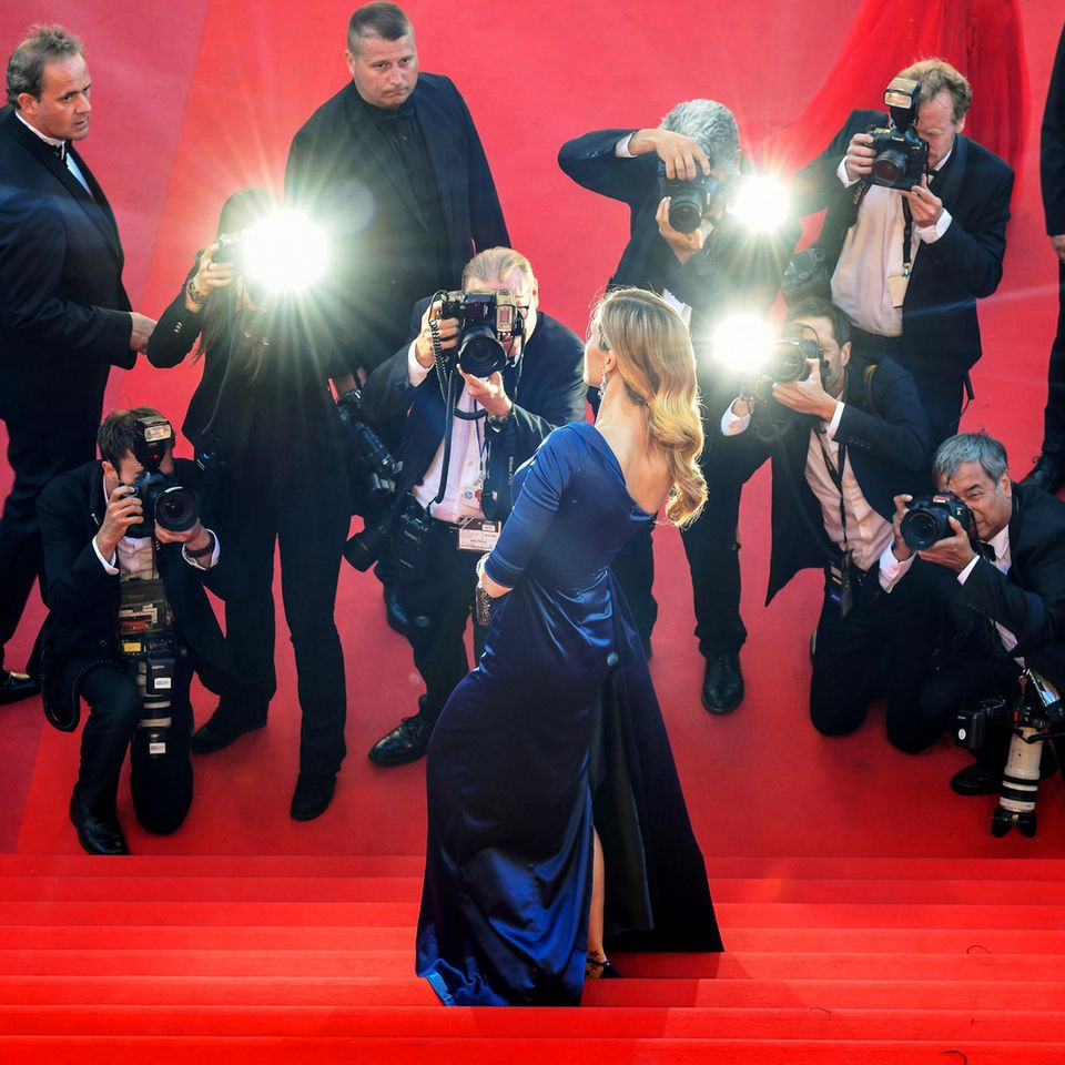 Star auf dem roten Teppich, umgeben von Fotografen
