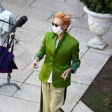 Tilda Swinton huscht im grünen Jackett vonHaider Ackermann durchs Bild - dazu trägt sie lila Loafer.