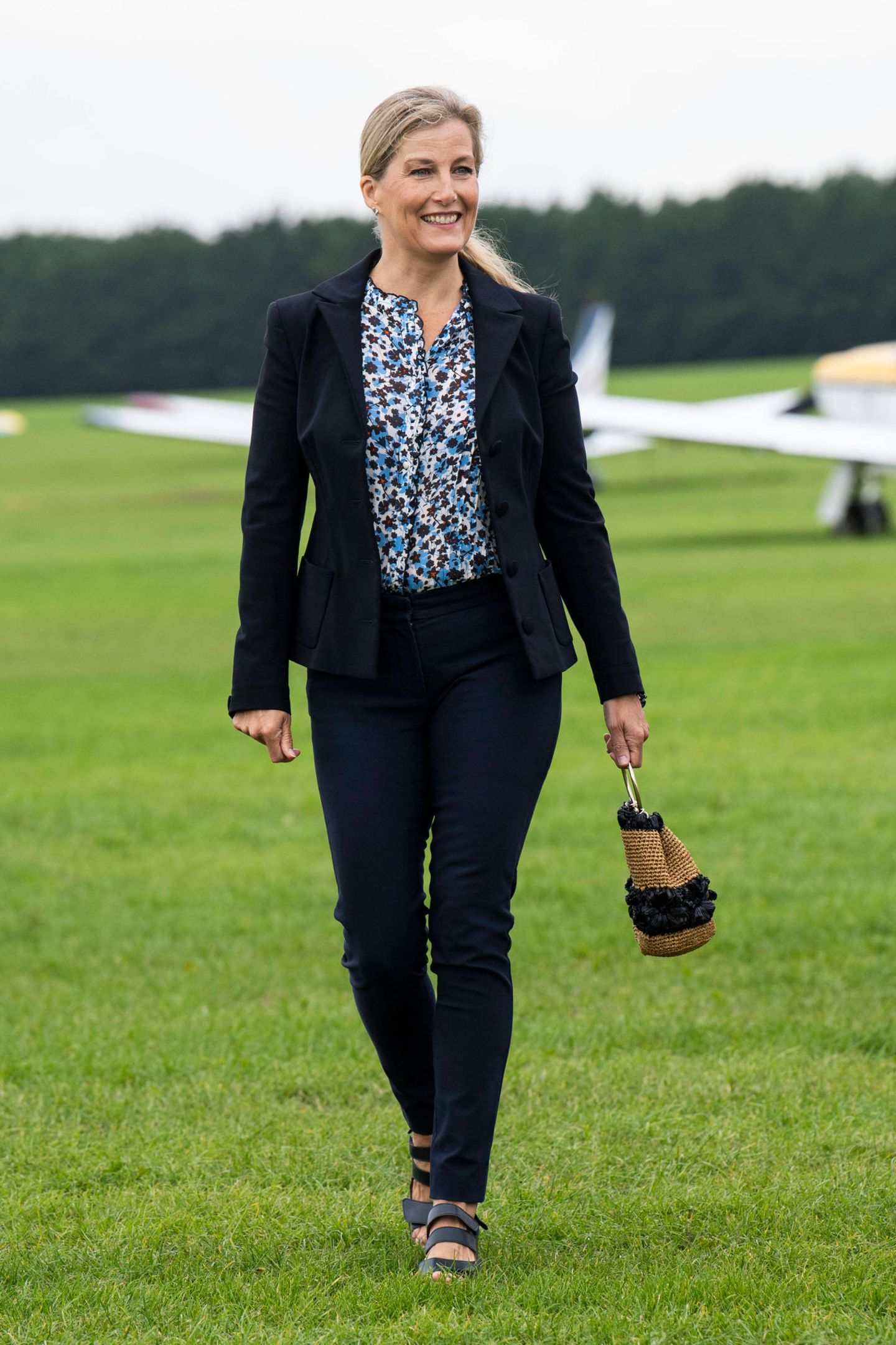 Gewohnt stilsicher zeigt sich Gräfin Sophie von Wessex bei einem Besuch der Luft-Ambulanz in Maidenhead. Zum dunkelblauen Zweiteiler kombiniert sie eine gemusterte Bluse und sommerliche Accessoires wie Bast-Tasche und Sandalen.