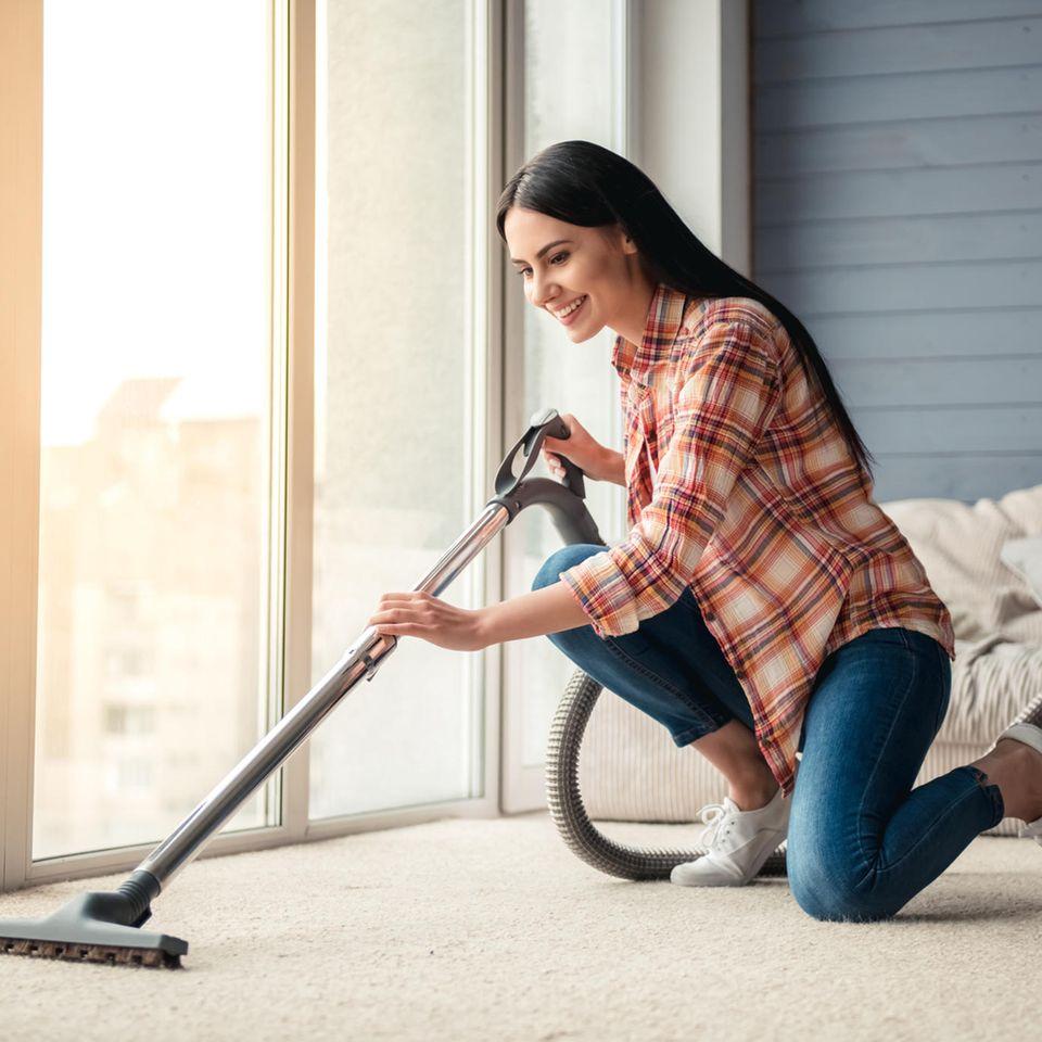 Staubsauger, junge Frau beim Staubsaugen, Frau saugt Wohnung