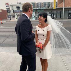 """Sängerin Lily Allen hat """"Ja"""" gesagt. In einem doppelreihig geknöpften Off-Shoulder-Kleid von Dior mit kurzen Ärmeln und mit voluminösem Tüll-Schleier heiratet sie den """"Stranger Things""""-Star David Harbour. Das dunkle Haar der Braut ist hochgesteckt und sie strahlt über das ganze Gesicht..."""