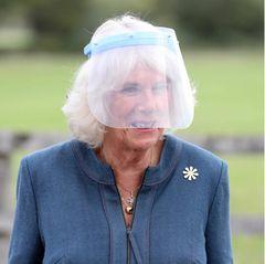 """Camilla erscheint erstmals mit einem Corona-Schutzvisier. Sie trage es, weil sie der Meinung sei,es sei""""einfacher zu kommunizieren"""", wenn man """"jemanden lächeln und sprechen sehen kann"""", berichtet Royal-Korrespondent Chris Ship."""