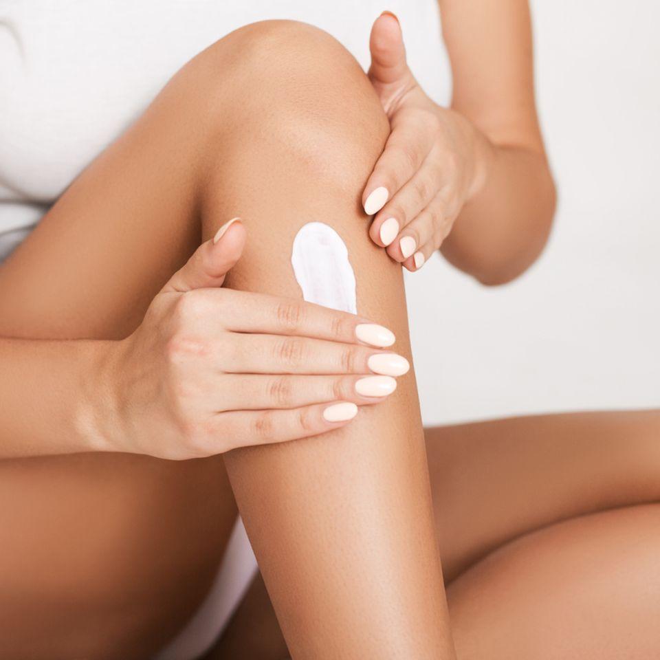 Frau wendet Feuchtigkeitscreme auf ihrem Körper an