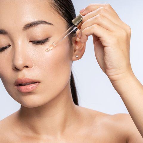 Asiatische Frau wendet Serum auf dem Gesicht an
