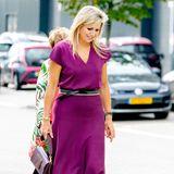"""Bei einem Besuch in Rotterdam beweist Königin Máxima Stilsicherheit: In einer kurzärmeligen Bluse mit V-Ausschnitt sowie einem farblich passenden Midi-Rock vom spanischen Label """"Massimo Dutti"""" besucht sieeine Firma für neue und gebrauchte Maschinen und Nutzfahrzeuge. Auf Arbeitsschuhe verzichtet die niederländische Königin trotzdem, zu ihrem Statement-Look kombiniert sie schlichte graue Pumps der italienischen Marke """"Natan"""", ihre Taille betont sie mit einem lässigen Bindegürtel. Das Highlight ihres Outfits trägt sie hingegen an der Hand ..."""