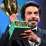 Der italienische SchauspielerPierfrancesco Favino hält stolz seine Coppa Volpi in die Luft. Er wurde in diesem Jahr als bester Darsteller ausgezeichnet.