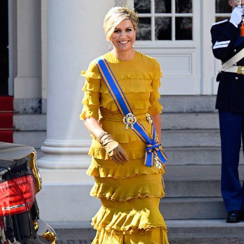 Wenn Königin Máxima kommt, geht die Sonne auf: Anlässlich desPrinsjesdag wirft sich die niederländische Königin ganz schön in Schale und trägt eine extravaganteCouture-Robe des niederländischen Designers Claes Iversen. Doch Máxima hat das Kleid nicht extra für den besonderen Tag anfertigen lassen: Sie trug das goldgelbeKleid mit Volants bereits 2018, als sie und ihr Mann, König Willem-Alexander, Besuch von König Abdullah und Königin Rania aus Jordanien bekamen. Und auch bei ihren Accessoires setzt sie auf altbewährte Pieces ...