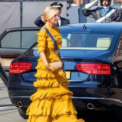 """Zu der Designer-Robe kombiniert Màxima hellbraune Lederhandschuhesowieihre goldene """"The Knot""""-Clutch vom LuxuslabelBottega Veneta, die sie bereits zuvor bei einigen Auftritten ausführte. Kosten: Rund 1.500 Euro, die Tasche ist in vielen Onlineshops ständig ausverkauft. Kein Wunder also, dass Màxima an wichtigen Tagen auf dieses stylische Accessoire vertraut."""