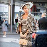Königin Máxima besucht die Eröffnung des Zuidplein-Theaters in Rotterdam. Sie trägt ein elegantes Tweed-Kostüm von Oscar de la Renta und hat eine klassische Tasche von Chanel dabei. Beige Pumps, Handschuhe und ein opulenter Fascinator runden den glamourösen Look ab.