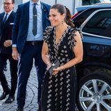 """Für dieSaisoneröffnung des Stockholmer Konzerthauses """"Konserthuset"""" setzt Prinzessin Victoria auf einen gekonnten Mix aus erschwinglicher und Luxus-Mode. Die Schwedin trägt ein schwarzes Couture-Kleid mit Blümchenmuster aus der exklusiven Giambattista-Valli-Kollektion für H&M, die im November letzten Jahres erschien. Dazu kombiniert sie eine glitzernde Clutch aus dem HauseSwarovski, schwarze Pumps und dezenten Schmuck, ihre Haare trägt Victoria in einem lässigen Pferdeschwanz. Ein stilvoller, gut durchdachter Look!"""