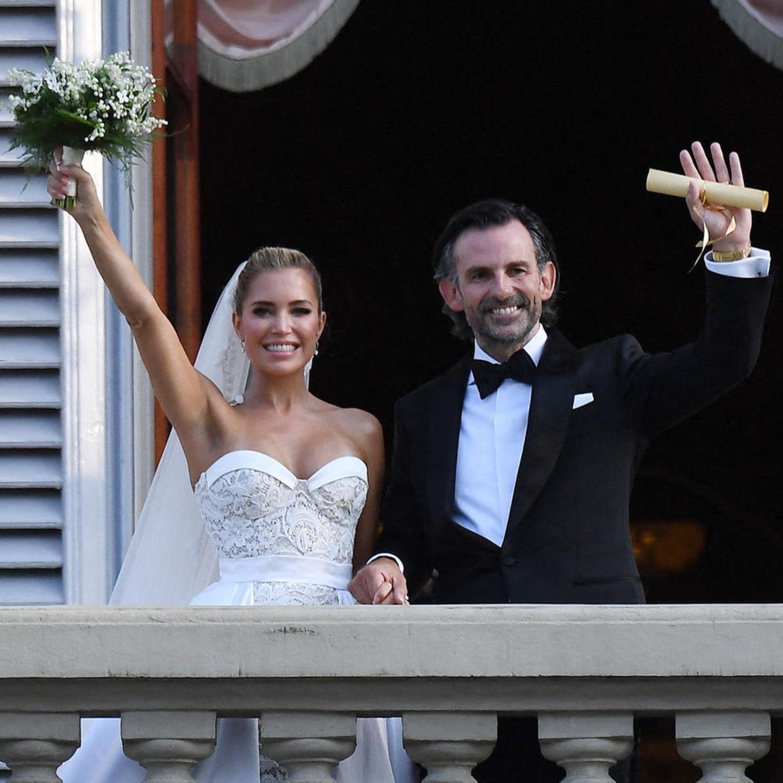 Glücklich winkt das frisch vermählte Hochzeitspaar vom Balkon.Niclas Castello hält seinenBräutigam-Look schlicht und verzichtet komplett auf Farben. Sylvie Meis ist mit ihrem Brautkleid styletechnisch ganz klar der Höhepunkt dieser Traumhochzeit.