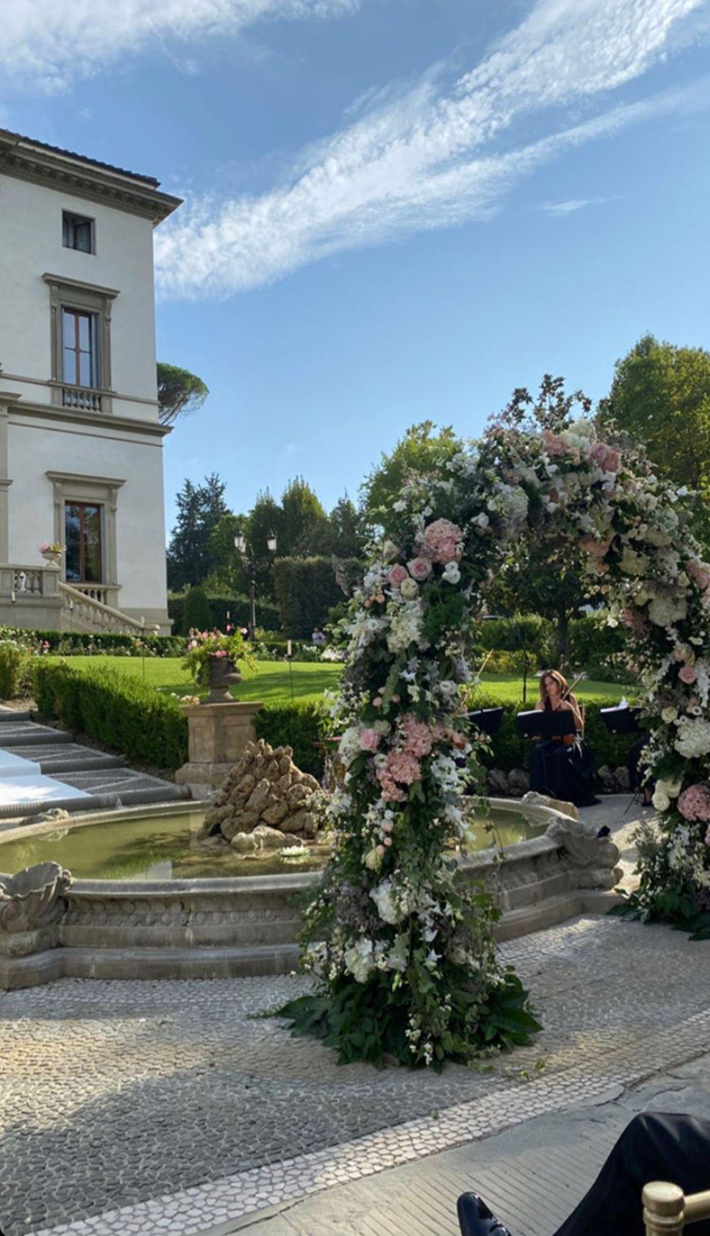 Wie aus einem Märchen! Die Hochzeit findet im Freien statt, vor einem Brunnen ist der Bogen aufgestellt, unter dem Sylvie Meis und Niclas Castello zum Ehepaar werden. Rosafarbene und weiße Blumen sind dort angesteckt. Im Hintergrund ist die Villa Cora, ein ehemaliger Adelssitz, am Ende des 19. Jahrhunderts gebaut, zu sehen.