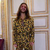 Content Creator Riccardo Simonetti hat noch einen zweiten Look parat: Für die Tanzfläche wechselt er in einen schwarzen Anzug mit goldenem Muster. Die leicht getönte Sonnenbrille und Gucci-Sneaker machen den Look perfekt.