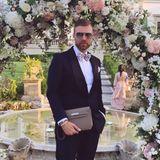 André Borchers posiert unter dem kunstvoll dekorierten Rosenbogen. Er trägt einen schlichten Smoking und setzt mit seinen Accessoires Akzente: Seine gepunktete Fliege, die Pilotenbrille und besonders die Hermès-Tasche ziehen alle Blicke auf sich.