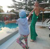 Haut-Guru Dr Barbara Sturm und ihre Tochter Peppertanzen am Pool. Barbara trägt ein grünes Slipdress mit tiefem Rückenausschnitt, die kleine Pepper setzt auf eine geblümte Hose, ein schlichtes T-Shirt und Sandalen.
