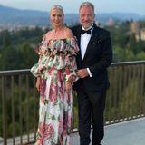 Petra van Bremen erscheint in einer eleganten Off-Shoulder-Robe von Dolce & Gabbana. Der Blumenprint passt perfekt zum Setting der Toskana. Ein Dutt und baumelnde Ohrringe runden den Look ab.