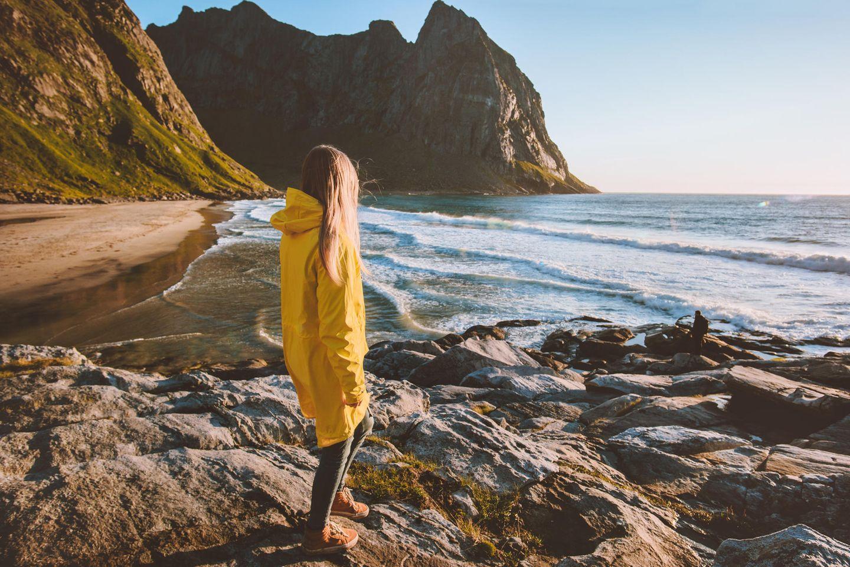 Frau in gelber Jacke schaut aufs Meer, Felsen und Strand