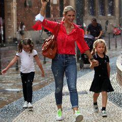 """Vom Regen überrascht lassen sich Michelle Hunziker und ihre Töchter Celeste und Sole nicht die Stimmung verderben. Während Michelle farblich aus dem Muster fällt, glänzen die beiden Schwestern in einemaufeinander abgestimmten Look. Beide Mädchen tragen die Haare zu zwei Zöpfen gebunden, T-Shirts mit dem gleichen """"SC""""-Emblem und dazu einen dunkelblauen Rock und Hose. Die Outfits erinnern an eine Schul- oder Sportuniform und geben den modischen Minis einen sportlichen Touch."""