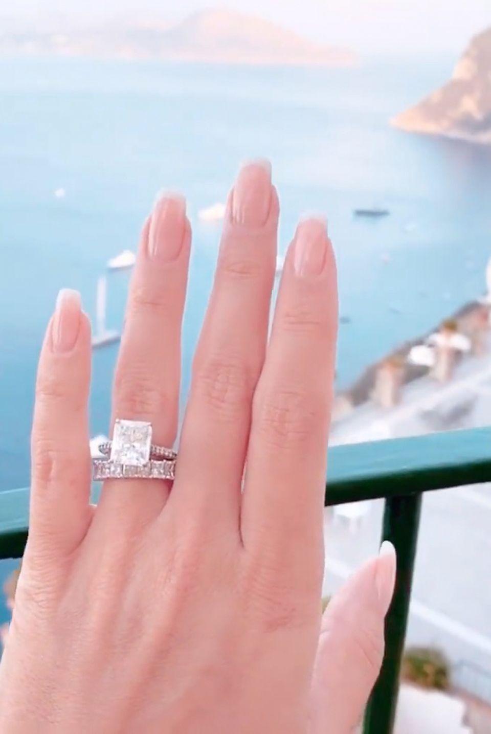 """Wow! Nach ihrer spektakulärenHochzeit in Florenz flittern Sylvie Meis und Niclas Castello nun auf der italienischen Insel Capri – und nehmen ihre Fans selbstverständlich mit. Vor traumhafter Kulisse präsentiert die frischgebackene Braut ihren mehr als 1,3 Millionen Instagram-Followern nun stolzihren Verlobungs- und Ehering. Ihren massiven Verlobungsring des US-amerikanischen Luxus-Juweliers """"Greene & Co. Diamonds"""" trägt Meis über ihrem funkelnden Ehering, der mit unzähligen Diamanten besetzt ist. Eine tolle Kombination!"""