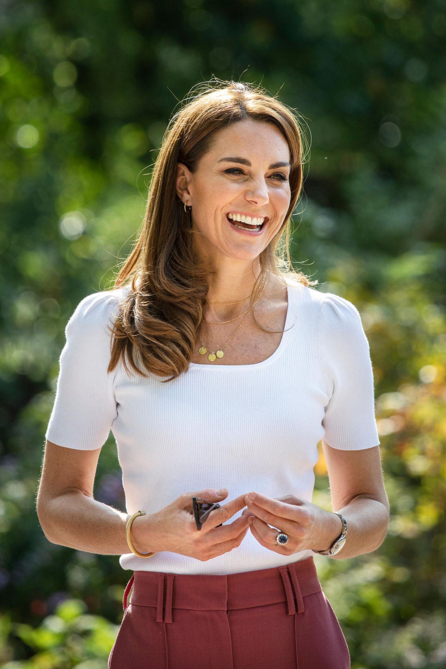 Mit ihrem strahlenden Lächeln macht sie den von der Coronapandemie gebeutelten Familien Mut. Und auch sie hat ihre Familie irgendwie bei sich: Im Ausschnitt ihres schlichten T-Shirts baumelt eine goldene Kette mitdrei Anhängern für Prinz George, Prinzessin Charlotte und Prinz Louis.