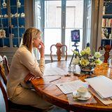 Dank des Stativs hat Königin Máxima genug Platz für Notizen, Stifte, Kaffeetassen und Co. und kann während des Calls sogar aufstehen, ohne von der Bildfläche zu verschwinden. Aus diesem Winkel bekommen wir außerdem einen neuen Eindruck ihres Arbeitszimmers: In zwei gläsernen Vitrinen sammelt die 49-Jährige Erinnerungsstücke, Teekannen und Bücher, außerdem stehen Bilderrahmen mit privaten Fotos der Königsfamilie in demeleganten Schaukasten.