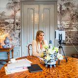 Willkommen im Homeoffice von Königin Máxima! Während einesvirtuellen Meetings im Rahmen der UN-Generalversammlung nimmt uns die niederländische Königin mit in ihr Büro in Den Haag – und das ist ganz schön extravagant! Die Wände werden von einer außergewöhnlichen Schwarz-Weiß-Tapete in Tropen-Optik geziert, auf einem antiken Beistelltisch davor steht sogar eine goldene Lampe in Form einer Palme. Máximas runder Arbeitstisch sowie die maritim wirkende Vase habenebenso Vintage-Charakter und sind ein gewagter Gegensatz zum Rest des Zimmers. So gar nicht Vintage ist hingegen das moderne Stativ, in dem die Königin gekonnt ihr iPad befestigt hat.