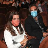 Charlotte Casiraghi und ihr Ehemann Dimitri Rassam besuchen das Théâtre Antoine in Paris. Charlotte trägt eine schlichte weiße Bluse und eine orangefarbene Maske. Auf ihrem Schoß liegt eine schwarze Wildledertasche. Sie ist ungeschminkt und trägt ihr brünettes Haar offen.