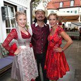 Stefanie Hertel (rechts) wird von ihrer bildhübschen Tochter Johanna (links) und Ehemann Lanny Lanner zum Oktoberfest begleitet. Beide Frauen setzen auf Rot: Johanna trägt eine rote Spitzenbluse und ein hellgraues Dirndl, Stefanie setzt komplett auf Rot.
