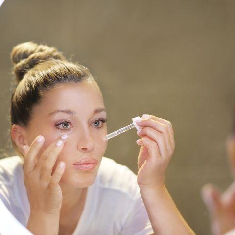 Frau trägt Anti-Aging-Serum vor dem Spiegel auf die Gesichtshaut auf