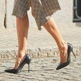 Zum karierten Business-Kleid kombiniert sie spitze High Heels von Manolo Blahnik und eine Clutch von Carolina Herrera - luxuriöse Accessoires mit Glam-Faktor.