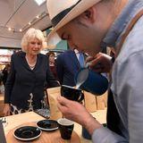 Gespannt beobachtet Herzogin Camilla den Barista beim Besuch der historischen Markthalle in Oxford bei der Arbeit.