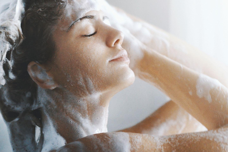Frau wäscht sich die Haare mit Shampoo unter der Dusche